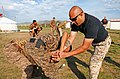 U.S. Marine Corps Gunnery Sgt. Herman Marquez, right, a nonlethal weapons instructor with the 3rd Law Enforcement Battalion, III Marine Expeditionary Force (MEF) Headquarters Group, III MEF, adjusts the hand 130819-M-MG222-002.jpg