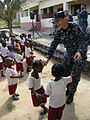 U.S. Navy Chief Musician Christopher Vlangas, assigned to the U.S. Naval Forces Europe Band ensemble Flagship, sings and dances with children at the Integracao Infantil Cristo Vida school in Nacala, Mozambique 120621-N-GA722-105.jpg