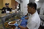U.S. Navy Information Systems Technician 1st Class Paul Labasan, right, selected for promotion to chief petty officer (CPO), assigned to the amphibious assault ship USS Makin Island (LHD 8), serves food at St 130827-N-QW737-060.jpg