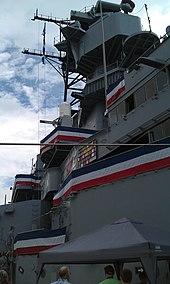 A photograph of the ship's superstructure as seen from deck level. The bridge, radar mast, and a phalanx gun are visible.