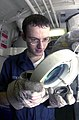 US Navy 030903-N-2143T-001 Aviation Structural Mechanic Airman John Watkins uses a magnifying glass to check for defects.jpg