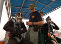 US Navy 050610-N-2385R-057 U.S. Navy divers assigned to the Ships Repair Facility- Japan Regional Maintenance Center, Detachment Sasebo get assistance with their gear in preparation for a diving evolution.jpg