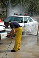 US Navy 050919-N-9458H-002 Dan Insardi of the New York City Fire Department, sprays a New Orleans Police Department patrol car as it drives through a decontamination station.jpg