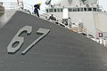 US Navy 060608-N-5055G-029 Sailors aboard USS Cole (DDG 67) haul in mooring lines to get the ship underway as part of the Iwo Jima Expeditionary Strike Group (ESG). Cole will deploy as part of the Iwo Jima Expeditionary Strike.jpg