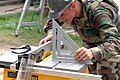 US Navy 070629-N-7088A-009 Builder 2nd Class Charles Page, assigned to Construction Battalion Maintenance Unit (CBMU) 202, adjusts a table saw while preparing to fix a fence at the Puerto Barrios Children's Hospital.jpg
