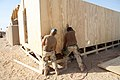 US Navy 081006-N-9623R-081 Seabees work constructing the wall on a South West Asia hut.jpg