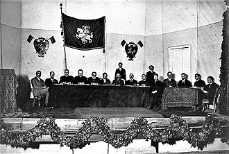 Vilnius Conference - Presidium and secretariat of the Vilnius Conference. The hall was decorated with small two-color (red and green) flags (three are visible in the picture). This was one of the suggestions for the Flag of Lithuania. The delegates decided it was too dark and gloomy and eventually a yellow stripe was added.
