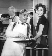 Photo en noir et blanc. William Demarest, en tablier blanc de serveur et tenant un plateau à la main s'appuie du dos contre un comptoir auquel est assise Cheryl Walker ; tous deux regardent, amusés, dans la direction du photographe.