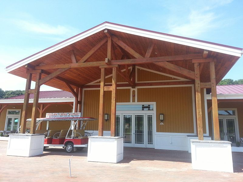A large wooden building with a red roof, three wooden posts, with an electric golf cart parked in front.