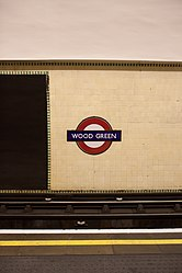 WoodGreen - Roundel and advertising on westbound platform after (4570824255).jpg