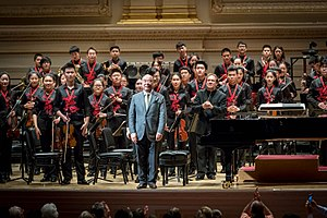 "Zhou Long - Zhou Long with conductor Ludovic Morlot and the National Youth Orchestra of China receiving applause for a performance of his original composition ""The Rhyme of Taigu"" at Carnegie Hall on July 22, 2017."