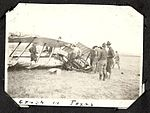"""Crash in Texas""- photograph of a group of men around a Royal Flying Corps aircraft which has been badly damaged in a crash, exposing the engine. (7980814125).jpg"