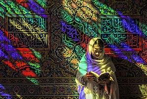 Une femme lisant un livre à la lumière des vitraux colorés ornant la mosquée Nassir-ol-Molk, à Chiraz. (définition réelle 5500×3726)