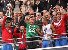 Players celebrating, one of whom is holding aloft a trophy