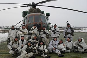 Soldiers in white in front of a helicopter