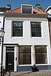 foto van Pand met verdieping en schilddak. Gevel onder houten kroonlijst. De verdiepingsvensters hebben zesruitsschuiframen
