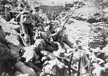 Soldiers with rifles, slouch hats and service caps sit on a steep escarpment behind a sandbagged trench