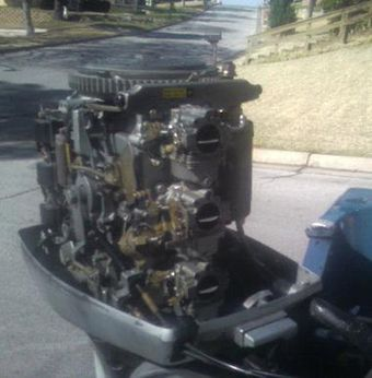 1979 Evinrude 70 hp outboard, cowling and air silencer removed, exposing its shift/throttle/spark advance linkages, flywheel, and three carburetors 79rude70.JPG