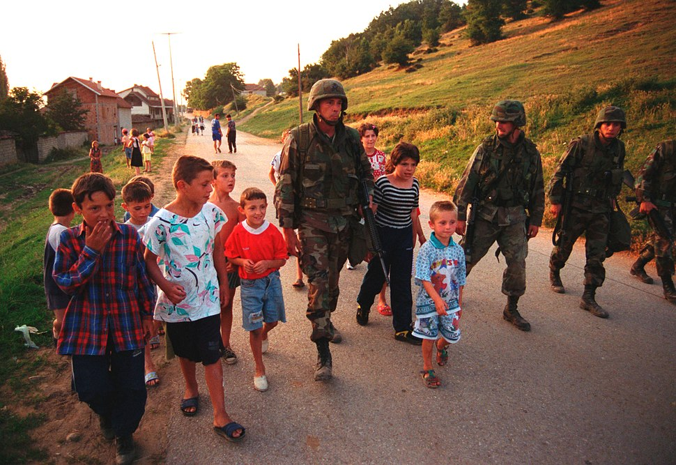 990628-M-5696S-025 - U.S. Marines march with local children down street of Zegra, Kosovo