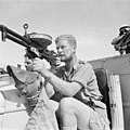 A member of a Long Range Desert Group (LRDG) patrol poses with a Vickers 'K' Gas-operated machine gun on a Chevrolet 30-cwt truck, May 1942. E12410.jpg