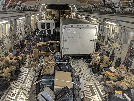 Photograph of the inside of a cargo jet, containing people in military field uniforms, equipment, and trucks