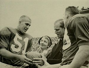 1957 Maryland Terrapins football team - Co-captains Gene Alderton (left) and Jack Healy present Prince Philip a game ball.