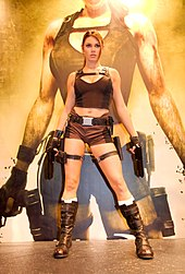 A woman in a Lara Croft outfit holding pistols upward her hands.