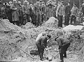 American troops with the 82nd Airborne Division look on as German exhume corpses from a mass grave.jpg