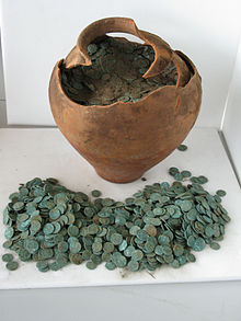 Earthenware pot on a table with coins inside it and in front of it