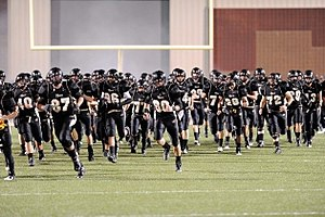 Bentonville High School - BHS Tiger Football Team entering the field at the beginning of a home game.