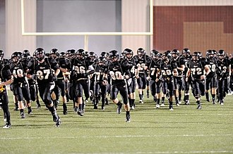 Bentonville High School - BHS Tiger football team entering the field at the beginning of a home game