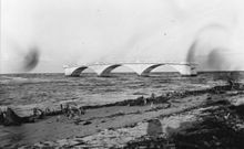 A black and white photograph of the ruins of a bridge taken from a beach with broken and uprooted trees recently damaged by a hurricane