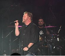 In a dark room, a singer holding a microphone in one hand and stand in the other is standing in front of a drummer