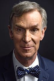 A close-up shot of Bill Nye's face, wearing one of his trademark bowties.