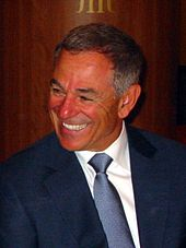 A man in a blue suit and a blue tie looks to his right and smiles.
