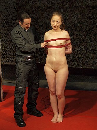 Bondage rigger - A male bondage rigger demonstrates to the audience on how to do rope bondage, at BoundCon 2015 event in Germany. The bondage technique used here is box tie, a basic form of arm and breast bondage.