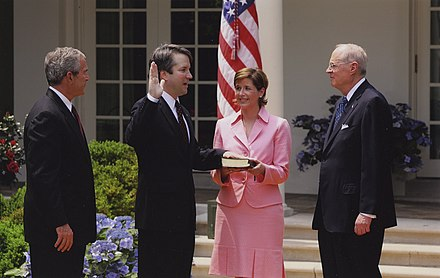 Kavanaugh is sworn into the D.C.Circuit by Justice Anthony Kennedy as his wife holds the bible and President Bush looks on, 2006. Coincidentally, Kavanaugh would be sworn into the U.S. Supreme Court 12 years later as Kennedy's replacement. Brett Michael Kavanaugh Takes Oath.jpg
