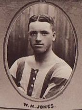 Head and upper torso of a stocky white man with dark hair parted in the middle. He is wearing a sports shirt with broad stripes.