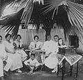COLLECTIE TROPENMUSEUM Groepsportret tijdens het luisteren naar een grammofoonplaat onder de beschutting van een palmboom TMnr 60046181.jpg