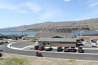 Celilo Village, Oregon - Modern Native American Longhouse in Celilo Village with the Columbia River and Oregon Trunk Rail Bridge in the background