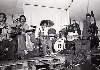 Diz Disley - Disley (right of centre) jams onstage with the Chris Newman group at the 1977 Cambridge Folk Festival