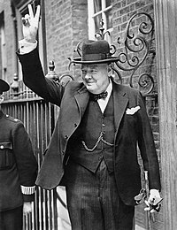 "A jowly, well-dressed man, obviously Winston Churchill, standing outside a doorway. He is smiling and making a ""V for victory"" gesture."