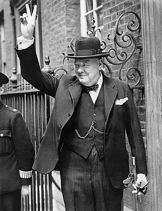 Homburg hat - Former UK Prime Minister Winston Churchill giving his 'V' sign during World War II on Downing Street, London, wearing a homburg hat with a black lounge suit with formal trousers, dotted bowtie, dark waistcoat, and a walking stick.