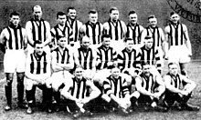 A group of men wearing sleeveless guernseys with black-and-white vertical stripes.