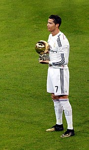 A man in a white shirt poses with a golden ball while standing on football pitch.