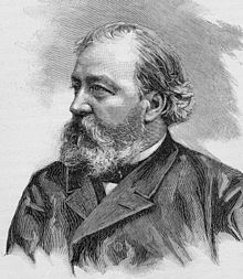 Head and shoulders of a middle-aged man wearing a coat, facing his right.  His receding hair is swept back and his beard is unruly, obscuring his mouth and chin.