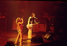 Roger Daltrey singing and Pete Townshend singing and playing a guitar