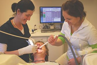 Dental assistant - Dental practitioner and dental assistant working in conjunction with one another.