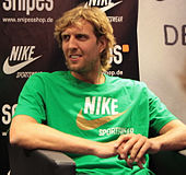 Dirk Nowitzki, seated, wearing a green Nike shirt