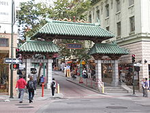 Photo of The Dragon Gate (looks like a small pagoda that you can walk under) as seen in 2008, opening onto Grant Avenue in San Francisco's Chinatown